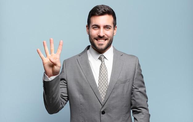Młody dorosły przystojny biznesmen uśmiechnięty i wyglądający przyjaźnie, pokazujący cyfrę cztery lub czwartą z ręką do przodu, odliczając w dół