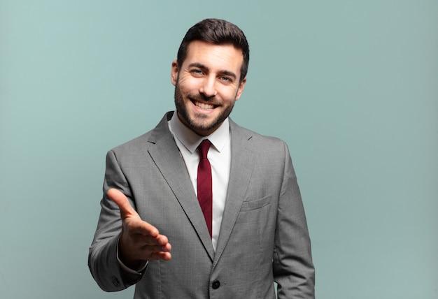 Młody dorosły przystojny biznesmen uśmiechnięty, wyglądający na szczęśliwego, pewnego siebie i przyjazny, oferujący uścisk dłoni, aby zamknąć transakcję, współpracujący