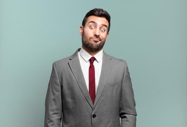 Młody dorosły przystojny biznesmen wyglądający głupkowato i zabawnie z głupim zezowatym wyrazem twarzy, żartując i wygłupiając się