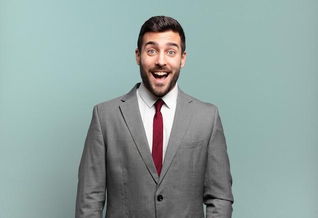 Młody dorosły przystojny biznesmen wyglądający na szczęśliwego i mile zaskoczony, podekscytowany zafascynowanym i zszokowanym wyrazem twarzy