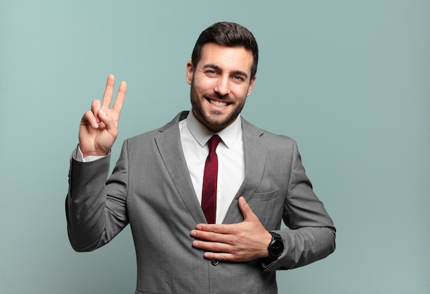 Młody dorosły przystojny biznesmen wyglądający na szczęśliwego, pewnego siebie i godnego zaufania, uśmiechnięty i pokazujący znak zwycięstwa, z pozytywnym nastawieniem