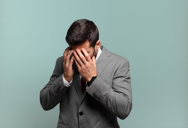 Młody dorosły przystojny biznesmen zakrywający oczy rękami ze smutnym, sfrustrowanym wyrazem rozpaczy, płaczu, widoku z boku