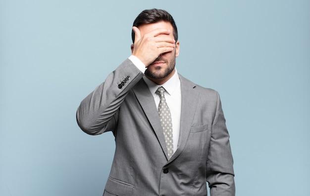 Młody dorosły, przystojny biznesmen zasłaniający oczy jedną ręką, czujący strach lub niepokój, zastanawiając się lub ślepo czekając na niespodziankę