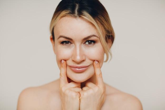 Młody dorosły robi masaż twarzy i ćwiczenia odmładzające budowanie twarzy w celu podnoszenia skóry i mięśni