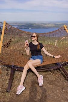 Młody dorosły szczęśliwy krótkowłosy ogolony łysy atrakcyjna kobieta chłodzenie cieszyć się relaksującym siedzeniem w hamaku na krześle z tkaniny na podwórku w garen w pobliżu domu. spokojny i sielankowy styl życia na świeżym powietrzu.