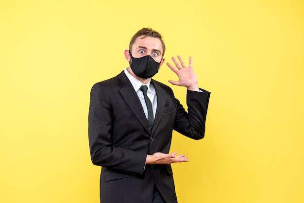 Młody dorosły w garniturze i pod krawatem mówi coś ważnego z podekscytowanym wyrazem twarzy na żółto