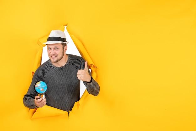 Młody dorosły w kapeluszu trzymający małą kulę ziemską i wykonujący ok gest ze szczęśliwym wyrazem twarzy w rozdartej na żółtej ścianie
