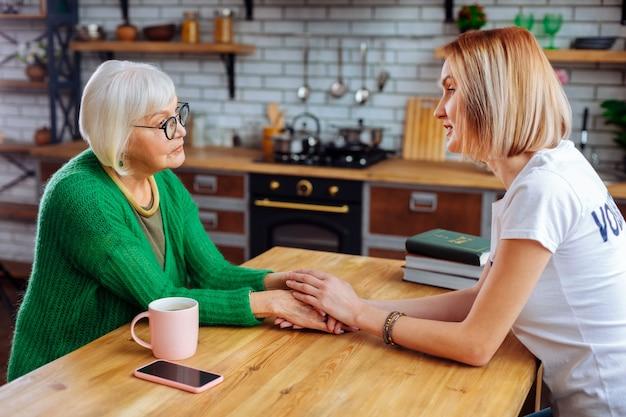 Młody dorosły wolontariusz rozmawia ze starzejącą się kobietą w kuchni