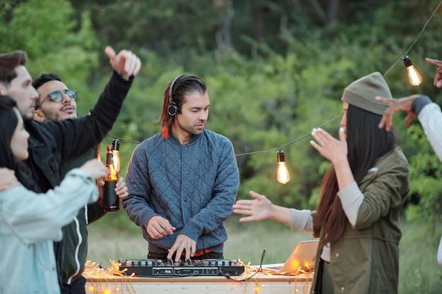 Młody dorywczo mężczyzna w kurtce i słuchawkach tworzy muzykę dla swoich radosnych międzykulturowych przyjaciół tańczących i cieszących się letnim weekendem