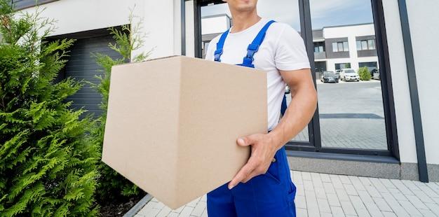Młody dostawca trzyma w rękach kartonowe pudełko
