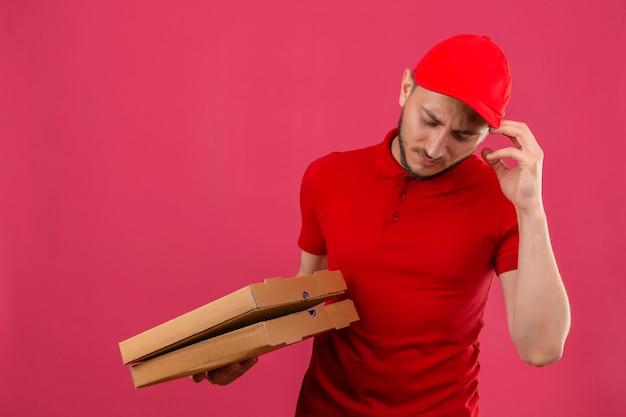 Młody dostawca ubrany w czerwoną koszulkę polo i czapkę pracuje pod presją z bólem głowy i problemami na odosobnionym różowym tle