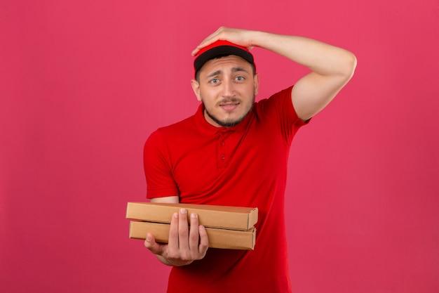 Młody dostawca ubrany w czerwoną koszulkę polo i czapkę stojącą z pudełkami po pizzy zaskoczony ręką na głowie za błąd pamięta błąd zapomniał złej koncepcji pamięci na izolowanym różowym tle