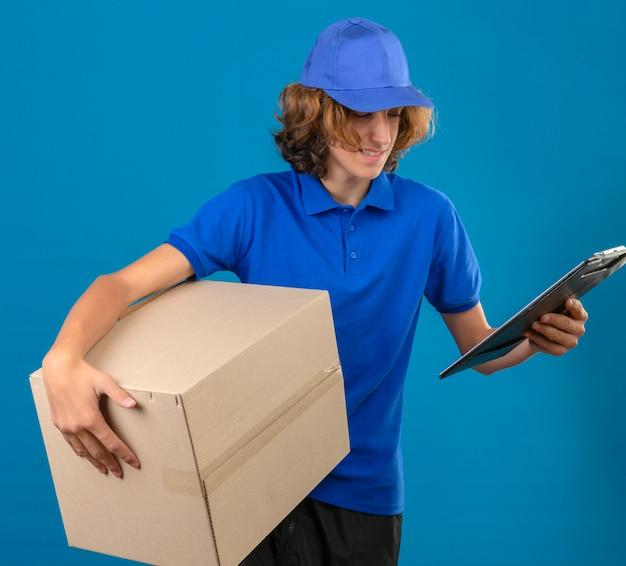 Młody dostawca ubrany w niebieską koszulkę polo i czapkę trzymający pudełko po pizzy i schowek z pustymi miejscami, uśmiechając się przyjazną stojącą ze szczęśliwą twarzą na izolowanym niebieskim tle