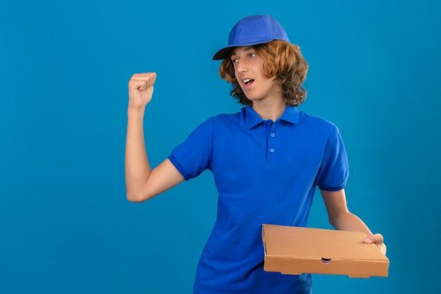 Młody dostawca ubrany w niebieską koszulkę polo i czapkę trzymający pudełko po pizzy wskazujący z tyłu ręką i kciukiem do góry, wyglądający na niezadowolonego na izolowanym niebieskim tle