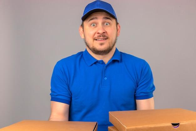 Młody dostawca ubrany w niebieską koszulkę polo i czapkę trzymający stos pudełek po pizzy wyglądający na zaskoczonego stojącego z szeroko otwartymi oczami z uśmiechem na twarzy na odosobnionym białym tle