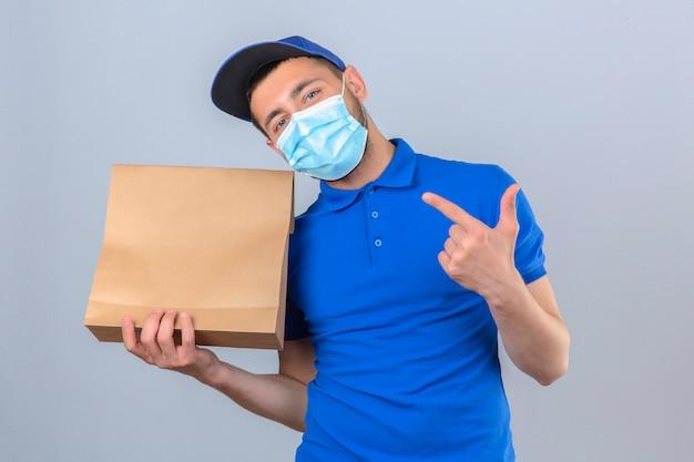 Młody dostawca ubrany w niebieską koszulkę polo i czapkę w ochronnej masce medycznej trzymający papierową paczkę z jedzeniem na wynos, wskazując na ten pakiet z uśmiechem na palcu nad izolowanym białym backgrou