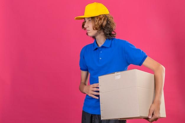 Młody dostawca ubrany w niebieską koszulkę polo i żółtą czapkę trzymający duże kartonowe pudełko w rękach patrząc na bok z poważną twarzą stojącą na izolowanym różowym tle