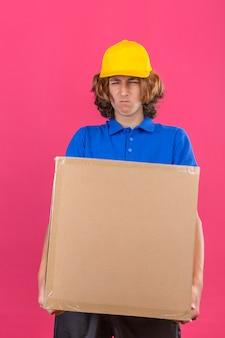Młody dostawca ubrany w niebieską koszulkę polo i żółtą czapkę trzymający duży duży, ciężki karton źle się czuje z powodu dużej wagi na izolowanym różowym tle