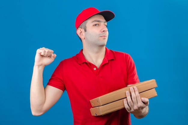 Młody dostawca w czerwonej koszulce polo i czapce trzymający pudełka po pizzy wyglądający pewnie na podniesienie pięści po koncepcji zwycięzcy zwycięstwa stojącej nad izolowaną niebieską ścianą