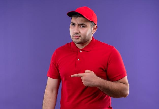 Młody dostawca w czerwonym mundurze i czapce wskazujący palcem w bok niezadowolony stojąc nad fioletową ścianą