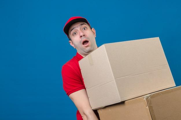 Młody dostawczyni w czerwonej koszulce polo i czapce trzymający duże, ciężkie kartonowe pudełko, czuje się zszokowany dużym ciężarem nad izolowaną niebieską ścianą