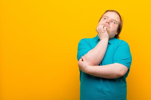 Młody, duży mężczyzna czuje się zamyślony, zastanawia się lub wyobraża sobie pomysły, marzy i szuka kopii miejsca na pomarańczowej ścianie