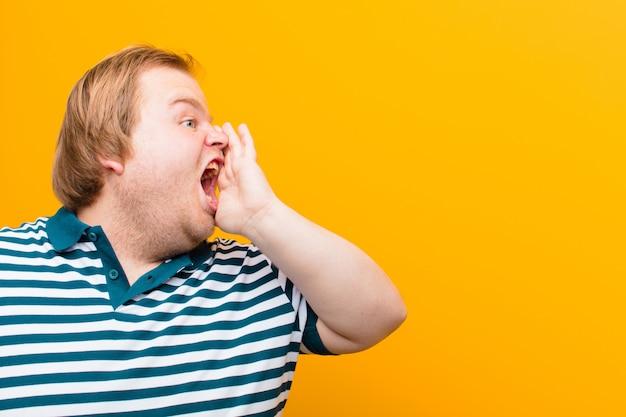 Młody, duży mężczyzna krzyczy głośno i ze złością, kopiując przestrzeń na boku, z ręką przy ustach na pomarańczowej ścianie