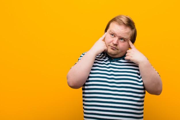 Młody, duży mężczyzna, skoncentrowany i intensywnie zastanawiający się nad pomysłem, wyobrażający sobie rozwiązanie problemu lub problemu z pomarańczową ścianą