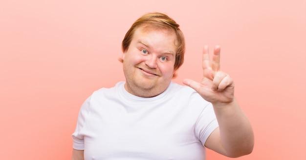 Młody, duży mężczyzna uśmiecha się i wygląda przyjaźnie, pokazuje numer trzy lub trzeci ręką do przodu, odliczając do różowej ściany