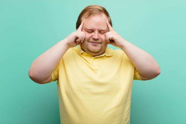 Młody, duży mężczyzna, wyglądający na skoncentrowanego, zamyślonego i natchnionego, burzy mózgów i wyobraźni z rękami na czole przy niebieskiej ścianie