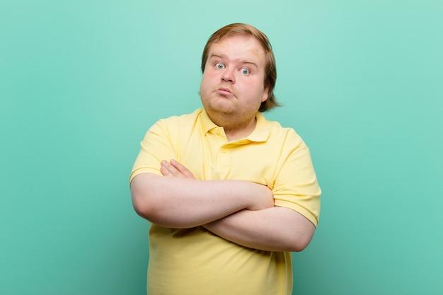 Młody, duży mężczyzna wzrusza ramionami, czuje się zmieszany i niepewny, wątpi ze skrzyżowanymi rękami i zdziwionym spojrzeniem na niebieskiej ścianie
