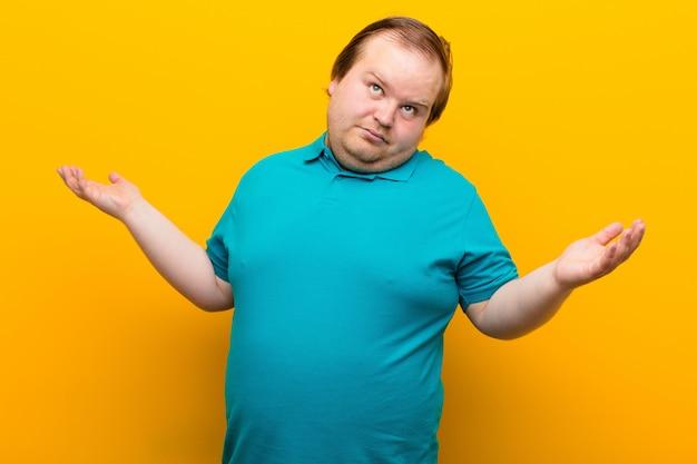 Młody, duży mężczyzna wzrusza ramionami z głupim, szalonym, zmieszanym, zdziwionym wyrazem twarzy, czuje się zirytowany i nieświadomy nad pomarańczową ścianą