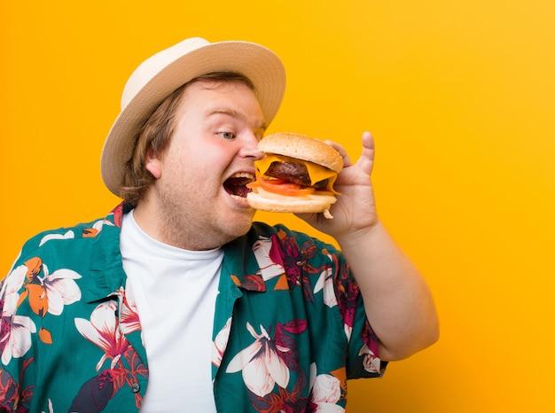 Młody, duży mężczyzna z burgerem z sera na płaskiej ścianie