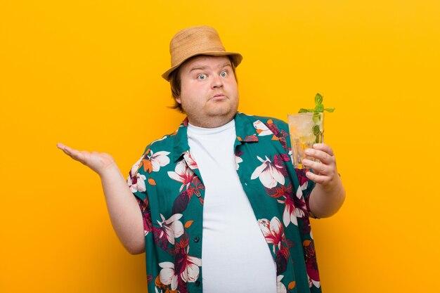 Młody duży mężczyzna z drinkiem mojito na płaskiej ścianie