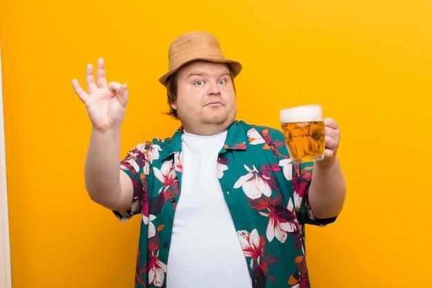 Młody, duży mężczyzna z kuflem piwa na płaskiej ścianie