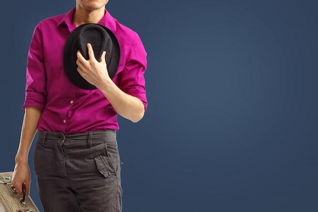 Młody dżentelmen zdjął kapelusz i przycisnął go do piersi na powitanie.