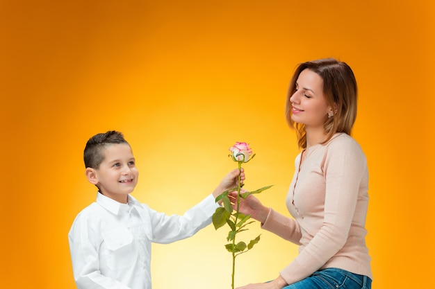 Młody dzieciak daje czerwoną różę swojej mamie