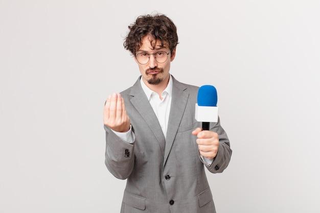 Młody dziennikarz robi gest kaprysu lub pieniędzy, każąc ci zapłacić