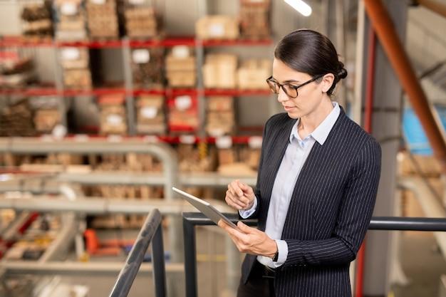 Młody ekspert od dużego zakładu przemysłowego przewijający na tablecie podczas surfowania po sieci w poszukiwaniu danych technicznych w miejscu pracy