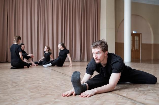 Młody elastyczny mężczyzna w czarnej odzieży sportowej siedzi w pozycji sznurka podczas treningu na podłodze z grupą tancerzy