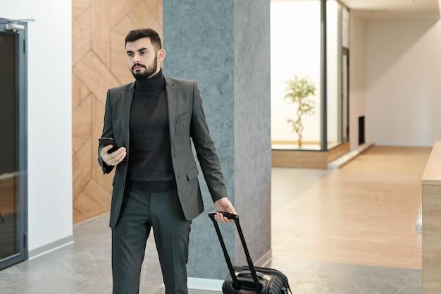 Młody elegancki biznesmen ciągnąc walizkę podczas poruszania się wzdłuż hotelowego salonu i czekając na recepcjonistkę