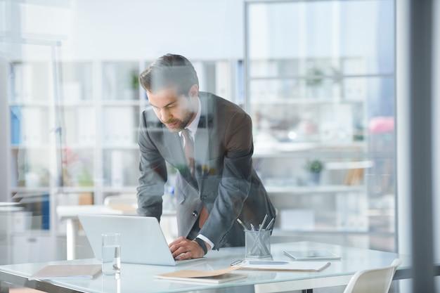 Młody elegancki biznesmen pochylając się nad biurkiem i laptopem podczas przeglądania sieci w biurze