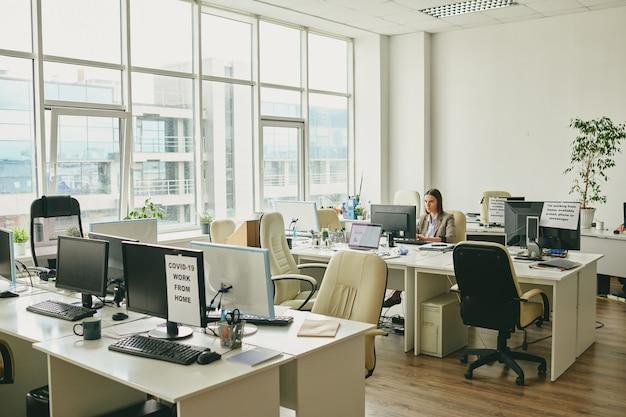 Młody elegancki bizneswoman siedzi przy biurku w rogu nowoczesnego biura i patrząc na ekran komputera w okresie pandemii