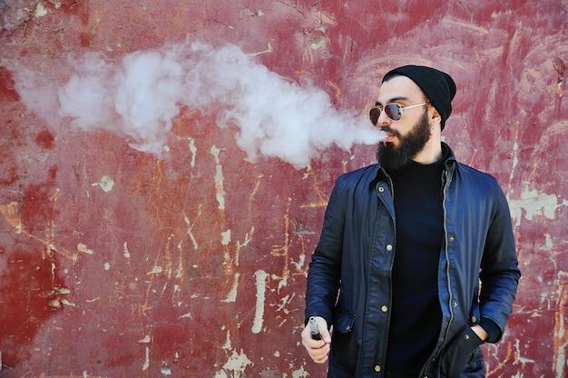Młody elegancki brodaty mężczyzna w czarnym kapeluszu z elektronicznym papierosem lub vape
