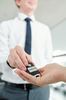 Młody elegancki kierownik sprzedaży, który oddaje system alarmowy zdalnego sterowania do ręki klientki przed jazdą próbną i zawieraniem transakcji