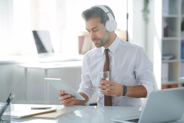 Młody elegancki, kreatywny projektant ze szklanką wody, słuchawkami i tabletem oglądającym wideo online w biurze