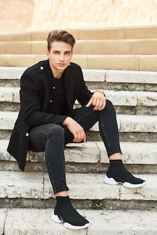 Młody elegancki mężczyzna w czarnych ubraniach