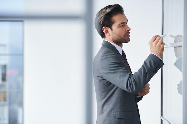 Młody, elegancki nauczyciel stoi przy przezroczystej tablicy i zapisuje punkty przedmiotu