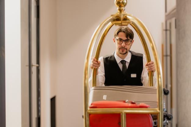 Młody, elegancki portier w okularach pchający wózek z bagażami gości hotelowych jadąc do przodu korytarzem