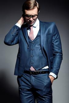 Młody elegancki przystojny biznesmen samiec model w błękitnym kostiumu i modnych szkłach pozuje w studiu